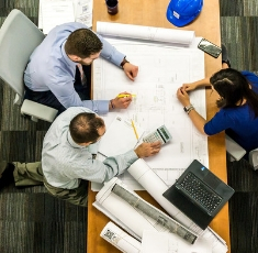 Employees with blue prints and table